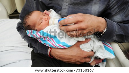 Close up of Newborn Infant Baby drinking formula from bottle - stock photo