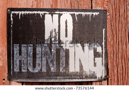 "Close-up of ""No Hunting"" sign on a decrepit barn"