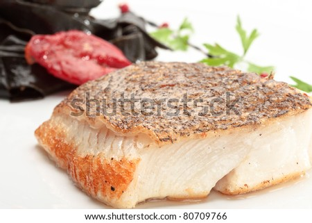 Close up of Norwegian halibut colorfully decorated on a white plate - stock photo
