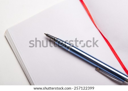 close up of note book with copy space on pages with pen - stock photo