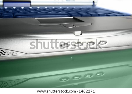 close-up of notebook/laptop lying on a green glass table - stock photo