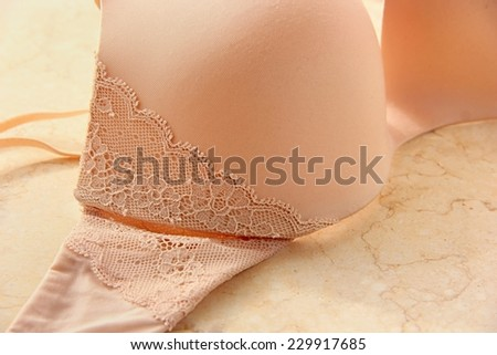 Close-up of nude color lace bra. - stock photo