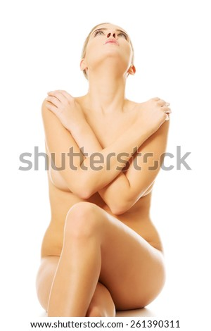 Close up of nude woman sitting on something invisible. - stock photo