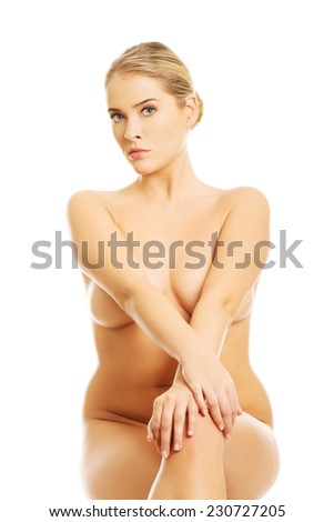 Close up of nude woman sitting with cross legs on something invisible. - stock photo