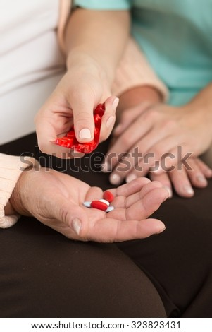 Close-up of nurse applying medicament for elder woman - stock photo