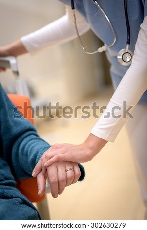 Close-up of nurse holding senior patient hand sitting in wheelchair