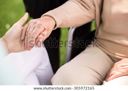 Close-up of nurse supporting disabled senior woman - stock photo