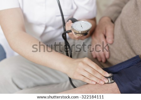 Close up of nurse taking old man blood pressure