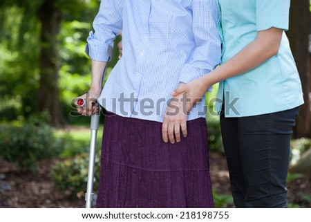 Close-up of nurse walking together with a female patient with a crutch - stock photo