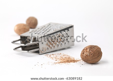 Close-up of nutmegs and grater on white background. Shallow dof - stock photo