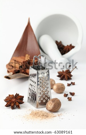 Close-up of nutmegs, cloves, anise and cinnamon with grater and mortar on white background. Shallow dof - stock photo