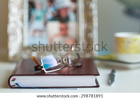 Close-up of office desk with notebook, pen and glasses - very shallow depth of field (soft focus)  - stock photo