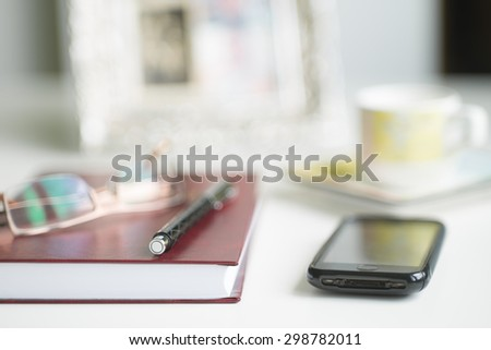 Close-up of office desk with notebook, pen, glasses and smartphone - very shallow depth of field (soft focus)  - stock photo
