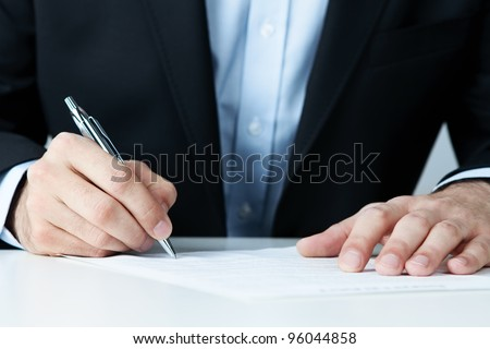 Close up of office worker filling documents - stock photo