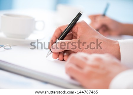 Close-up of office workers being ready to take notes - stock photo