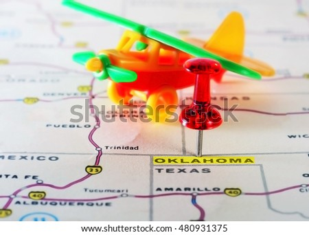 Close up of  Oklahoma  USA map with red pin and airplane  toy - Travel concept