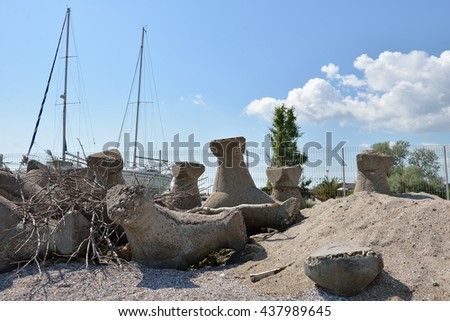 Close up of old and broken tetrapods made of concrete buried in sand at the beach, need to yacht harbor - stock photo