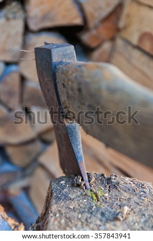 Close up of  old ax stuck in tree stump, woodpile on background. - stock photo