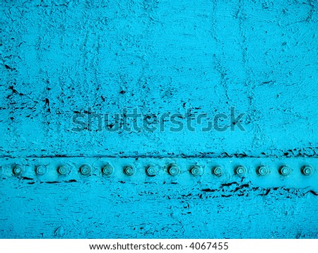 Close-up of old, cracked, dirty teal paint with the black base showing through and a line of bolts running across the surface - stock photo