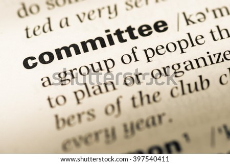 Close up of old English dictionary page with word committee - stock photo