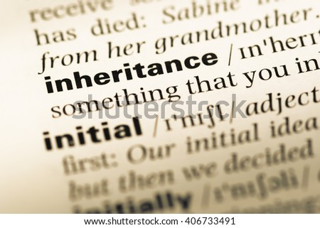 Close up of old English dictionary page with word inheritance - stock photo