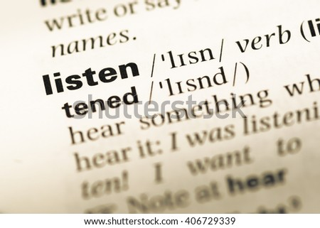 Close up of old English dictionary page with word listen - stock photo