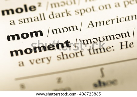 Close up of old English dictionary page with word mom - stock photo