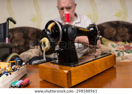 Close Up of Old Fashioned Sewing Machine Surrounded by Various Colorful Threads - Senior Man Behind Vintage Sewing Machine in Living Room - stock photo