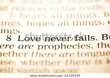 "Close up of old Holy bible book, The word ""Love never fails"". - stock photo"