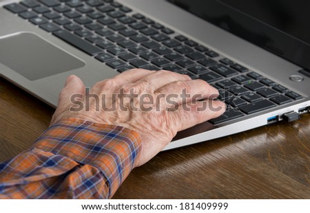 Close up of old man hand on keyboard of laptop - stock photo