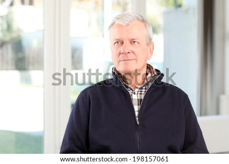 Close-up of old man sitting at sofa.  - stock photo