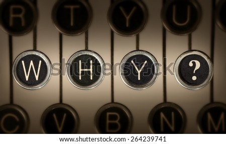 "Close up of old manual typewriter keyboard with scratched chrome keys that spell out ""WHY?"".  Lighting and focus are centered on ""WHY?""."