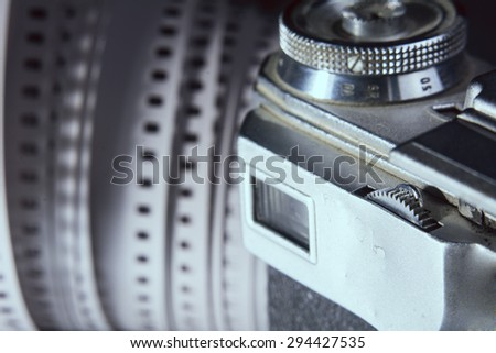 Close-up of old photo camera viewfinder and photo film 35 mm on the background. - stock photo