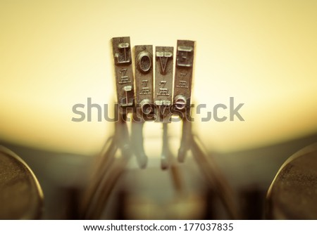Close up of old typewriter keyboard with scratched chrome keys that spell out LOVE. Lighting and focus are centered on LOVE.  - stock photo