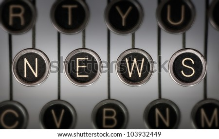 "Close up of old typewriter keyboard with scratched chrome keys with black centers and white letters. Lighting and focus are centered on for keys spelling out ""NEWS"". - stock photo"