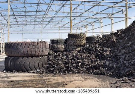 Close up of old used tires and shredded tire pile in background - stock photo