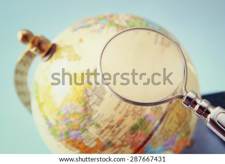 close up of old vintage globe and magnifying glass - stock photo