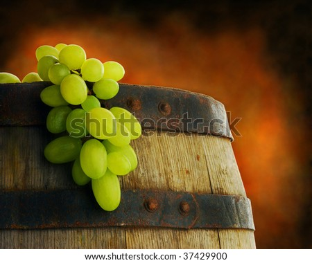 Close up of old wine barrel with grape cluster - stock photo