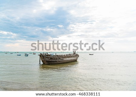 Close up of old wooden fisherman boat anchored near the beach in the evening.