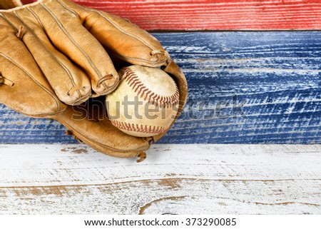 Close up of old worn baseball mitt and baseball on faded wooden boards painted red, white and blue.
