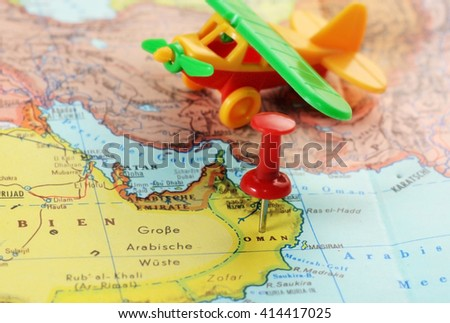Close up of  Oman   map with red pin and airplane toy  - travel concept