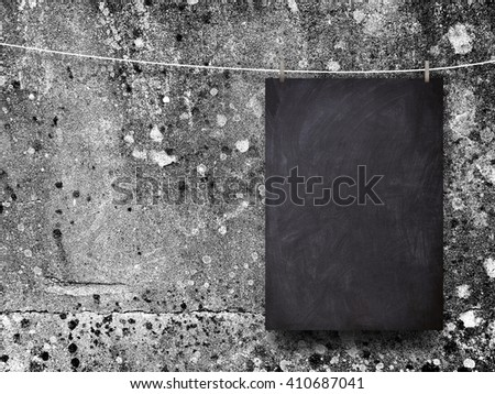 Close-up of one blank blackboard frame hanged by pegs against grey cracked concrete wall background