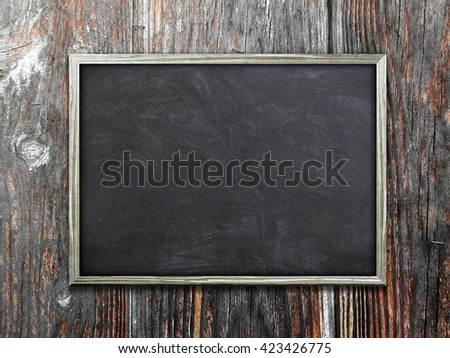 Close-up of one blank blackboard poster frame on dark brown wooden boards background