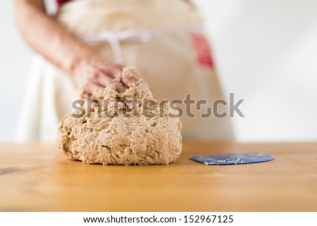 Close-up of one female hand kneading dough on a wooden table - stock photo