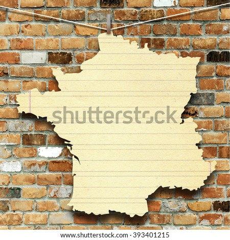 Close-up of one hanged France blank silhouette old paper sheet frame against brick wall background