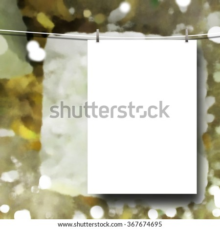 Close-up of one hanged paper sheet with clip on brown out of focus multicolour background