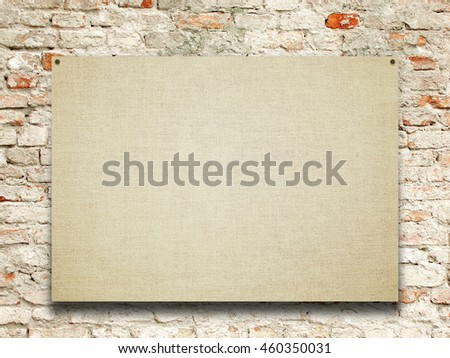 Close-up of one nailed blank poster canvas frame on old weathered brick wall background