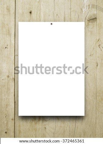 Close-up of one paper sheet with nail on brown wooden boards background