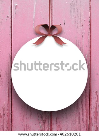 Close-up of one round blank frame hanged by red ribbon against pink weathered wooden boards background - stock photo