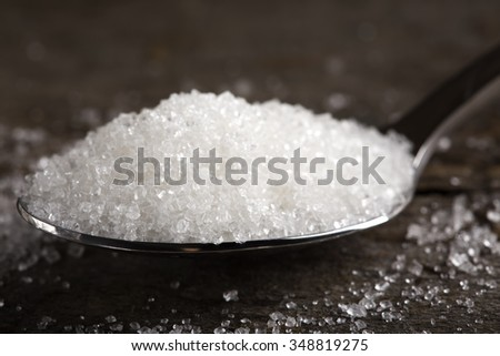 Close up of one spoon filled with sugar - stock photo